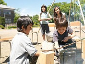 Four children 5-9 cooking in school playground