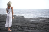 Mature woman standing on rocks looking out to ocean
