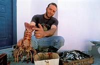 Fisherman showing lobster, basket of fish, Chora  Anafi, Cyclades, Greece, Europe
