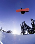 Snowboarder jumping in half pipe, low angle view
