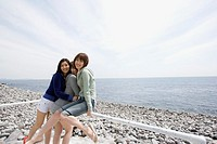 Three young women sitting on railing by ocean, hugging, smiling, portrait