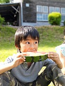 Boy 5-7 eating watermelon outdoors