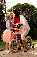 Mother on daughter´s 6-8 bicycle in garden, face to face
