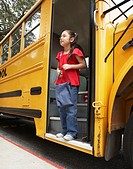 Girl 8-9 stepping off school bus, side view