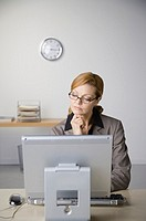 Mature businesswoman sitting at desk in office, using computer