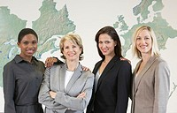 Four businesswomen standing in front of wall map of North America and Europe, group portrait