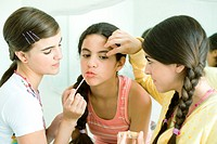Two young female friends putting make-up on younger girl