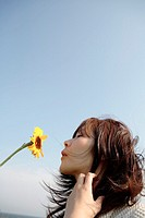 Woman facing sunflower, head and shoulders, profile