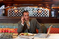 Portrait of business man using mobile phone at restaurant table, newspaper and laptop by plate
