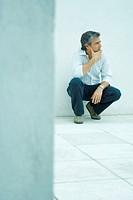 Mature man crouching, looking away, full length portrait