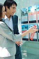 Couple standing next to window of real estate agency, looking at for rent and for sale signs