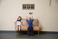 Girl 6-7 sitting on sofa, boy 21-24 months throwing doll in air