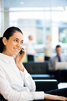 Young businesswoman sitting in lobby, using cell phone, smiling