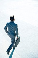 Young businessman running outdoors, carrying briefcase, rear view, high angle view