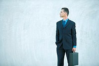 Businessman standing, carrying briefcase, looking away