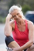 Active senior woman, in pink sports vest and leggings, sitting on driveway, smiling, front view, portrait