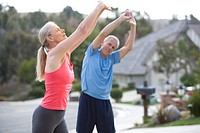 Active senior couple, in sportswear, warming up on driveway, stretching arms above head
