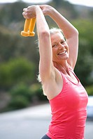 Active senior woman, in pink sports vest, exercising with dumbbells on driveway, lifting weights above head, smiling, side view, portrait