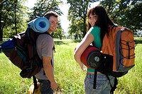 Young couple standing in woodland clearing on camping trip, carrying rucksacks and sleeping bags, looking over shoulder, smiling, rear view, portrait