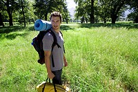 Young man standing in woodland clearing on camping trip, carrying rucksack, tent bag and sleeping bag, smiling, side view