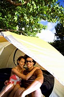 Young couple embracing in dome tent entrance on camping trip, smiling, front view, portrait