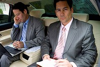 Two businessmen sitting in backseat of car, one man using laptop and mobile phone, portrait of man holding folder and pen