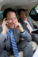 Two businessmen sitting in backseat of car, focus on man using mobile phone in foreground, smiling