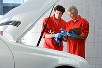 Two car mechanics, in red overalls and protective gloves, looking at car engine in auto repair shop, talking, mature man holding clipboard, side view