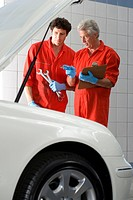Two car mechanics, in red overalls and protective gloves, looking at car engine in auto repair shop, talking, mature man holding clipboard, colleague ...