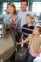 Family checking in at airport check-in counter, smiling