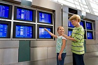 Brother 8-10 and sister 7-9 looking at flight information screen in airport departure lounge, girl pointing, smiling
