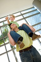 Father carrying son 8-10 on shoulders in airport, boy holding toy aeroplane, smiling, low angle view tilt