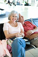 Senior couple sitting in airport departure lounge, man leaning on womanÔÇÖs shoulder, sleeping, woman smiling, portrait