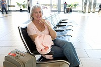 Senior woman sitting in airport departure lounge, holding pink jacket, smiling, side view, portrait