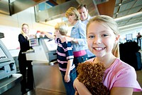Family receiving ticket from female flight check-in attendant at airport check-in counter, focus on girl 7-9 holding soft toy in foreground, smiling, ...