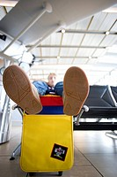 Boy 8-10 sitting with feet up on colourful bag in airport departure lounge, focus on soles of shoes in foreground