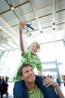 Father carrying son 8-10 on shoulders in airport, boy holding toy aeroplane, smiling, low angle view