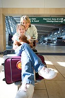 Woman standing beside luggage trolley in airport, daughter 7-9 sitting on suitcase with soft toy, smiling, front view, portrait
