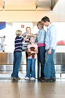 Family checking in at airport check-in desk, female check-in attendant passing boarding passes to boy 8-10, smiling, rear view