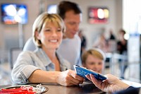 Family standing at airport check-in desk, woman receiving boarding passes from check-in attendant, smiling, focus on foreground