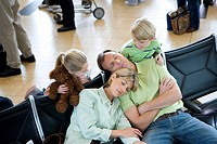 Family waiting in airport departure lounge, boy 8-10 and girl 7-9 watching parents sleeping, smiling, elevated view