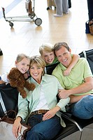 Family sitting in airport departure lounge, girl 7-9 holding soft toy, smiling, portrait, elevated view