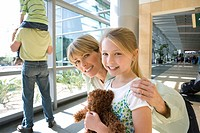 Boy 8-10 sitting on fatherÔÇÖs shoulders beside window in airport, focus on mother and daughter 7-9 in foreground, smiling, portrait