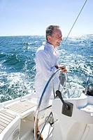 Mature man standing at helm of yacht out at sea, steering, smiling, side view