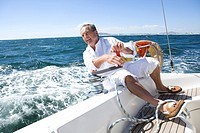 Mature man sitting on deck of yacht out at sea, leaning over side of boat, turning rope pulley, smiling