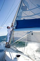 Mature man standing on deck of yacht out at sea, making adjustments to sail, side view tilt
