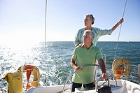 Mature couple sailing out at sea, man standing at helm of yacht, steering, woman looking at view from stern, hand on manÔÇÖs shoulder, front view back...