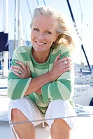 Mature woman, in green striped jumper, sitting on deck of yacht moored at harbour jetty, hugging chest, smiling, close-up, front view, portrait