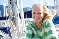 Mature woman, in green striped jumper, sitting on deck of yacht moored at harbour jetty, smiling, close-up, portrait