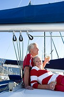 Mature couple, in red jumper and t-shirt, sitting on deck of yacht moored at harbour jetty, drinking white wine, woman leaning contentedly against man...